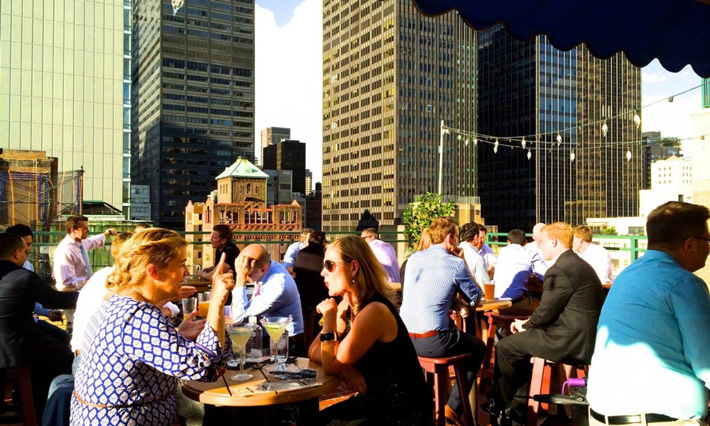 besucher im sonnenschein auf der rare view rooftop-bar